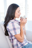 Pretty brunette holding hot beverage on couch Stock Photo