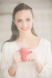 Pretty brunette holding a mug Royalty Free Stock Image
