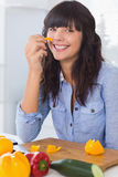 Pretty brunette holding piece of pepper Royalty Free Stock Photography