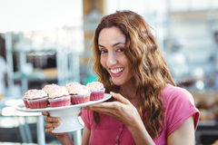 Pretty brunette holding plate of pastries Royalty Free Stock Image