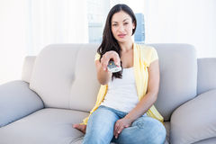 Pretty brunette holding remote control on couch Royalty Free Stock Photo