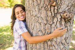 Pretty brunette hugging tree Royalty Free Stock Image