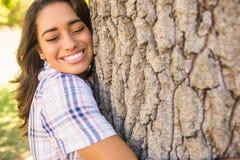 Pretty brunette hugging tree Royalty Free Stock Photos
