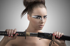 Brunette in japan style with katana turned of three quarters Royalty Free Stock Photos