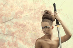 Brunette in japan style with katana looks at right Royalty Free Stock Photography