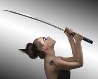 Brunette in japan style with katana turned at left Royalty Free Stock Image