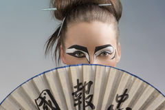 Pretty brunette in japan style with fan on the face Royalty Free Stock Photography
