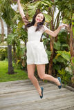 Pretty brunette jumping up and smiling Stock Images