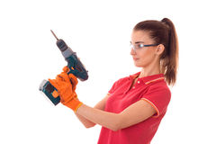Pretty brunette lady makes refurbish an apartment with drill in hands isolated on white background in studio Stock Images