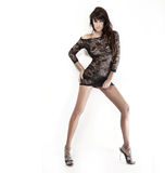 Pretty brunette lady wearing short black dress and posing over w. Pretty brunette lady with beautiful legs wearing short black dress and posing over white Stock Photography