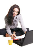 Pretty brunette with laptop writing at notebook Royalty Free Stock Photos