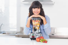 Pretty brunette leaning on her juicer full of fruit Royalty Free Stock Photo