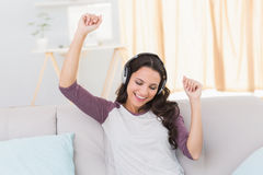 Pretty brunette listening to music on the couch Royalty Free Stock Image