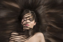 Brunette with long smooth hair looks down Royalty Free Stock Image