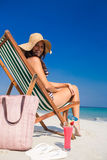 Pretty brunette looking at camera on deck chair Stock Images