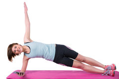 Pretty brunette looking at camera and doing side plank on exercise mat Royalty Free Stock Photography