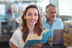 Pretty brunette looking at camera and holding book Stock Photo