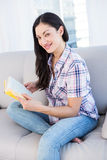 Pretty brunette looking at camera and holding a book on couch Stock Photos