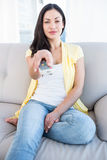 Pretty brunette looking at camera and holding remote control on couch Stock Photo