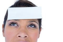 Pretty brunette looking at camera with paper on head Stock Photography