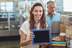 Pretty brunette looking at camera and showing tablet Stock Photography