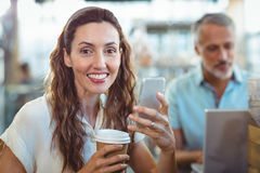 Pretty brunette looking at camera with smartphone and coffee in her hands Stock Photography