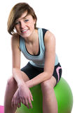 Pretty brunette looking at camera and smiling on fitness ball Stock Images
