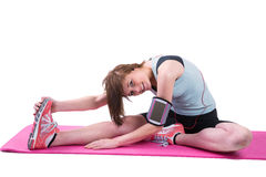 Pretty brunette looking at camera and stretching her leg on exercise mat Royalty Free Stock Photo
