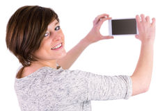 Pretty brunette looking at camera and taking a picture with her smartphone Royalty Free Stock Photography
