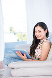 Pretty brunette looking at camera and using laptop on couch Royalty Free Stock Photo