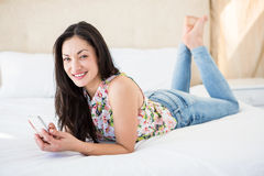 Pretty brunette looking at camera and using smartphone on bed Royalty Free Stock Images