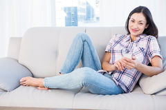 Pretty brunette looking at camera and using smartphone on couch Royalty Free Stock Image