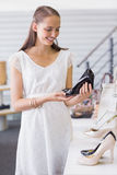 Pretty brunette looking at a heel shoe Stock Photo