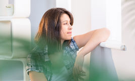Pretty brunette looking out her window Stock Photo