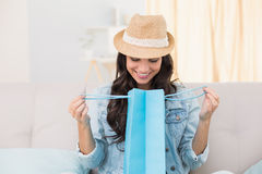 Pretty brunette looking in shopping bag. At home in the living room Stock Image