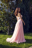 Pretty brunette in luxurious dress posing at park Stock Photography