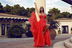 Pretty brunette in luxurious red dress posing at villa Royalty Free Stock Photos