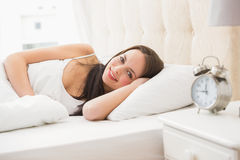 Pretty brunette lying in bed Stock Images