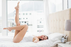 Pretty brunette lying on bed posing Royalty Free Stock Photos