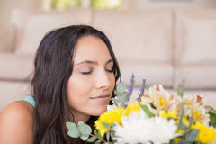 Pretty brunette lying on the floor and smelling the flowers Royalty Free Stock Image
