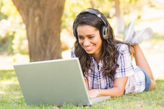 Pretty brunette lying in the grass and using laptop Royalty Free Stock Image