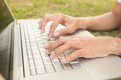 Pretty brunette lying in the grass and using laptop Stock Images