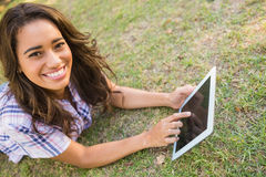 Pretty brunette lying in the grass and using tablet Stock Photo