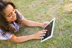 Pretty brunette lying in the grass and using tablet Royalty Free Stock Image
