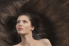 Girl with long brown hair looks up Stock Photo