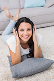 Pretty brunette lying on the rug listening to music Stock Image