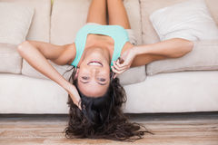 Pretty brunette lying upside down on couch. At home in the living room Royalty Free Stock Photography