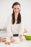 Pretty brunette making dough on counter Royalty Free Stock Image