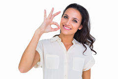Pretty brunette making ok sign. On white background royalty free stock photo