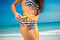 Pretty brunette measuring waist at the beach Royalty Free Stock Image